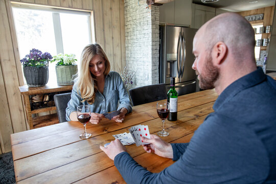 Couple playing cards at dining table with wine