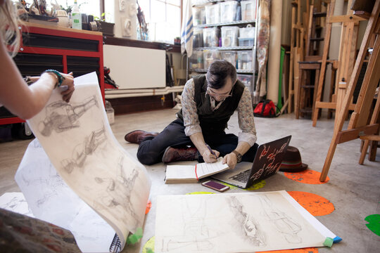 Artists sketching and planning on floor in art studio
