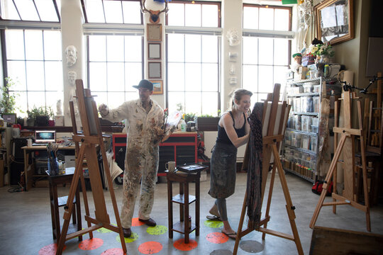 Artists painting and sketching at easels in creative art studio