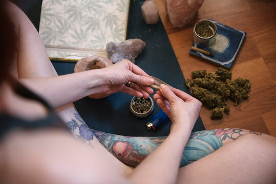 Woman with tattoos rolling marijuana joint