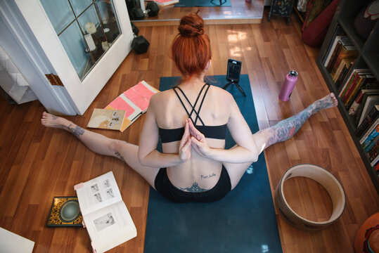 Flexible woman with smart phone and books practicing yoga at home