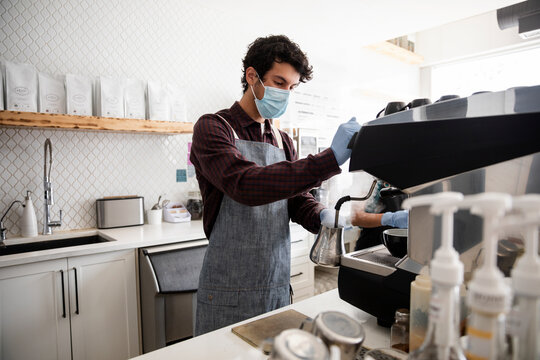 Young male barista in face mask working in cafe