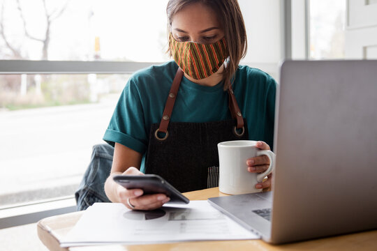 Young female business owner in face mask working at cafe table