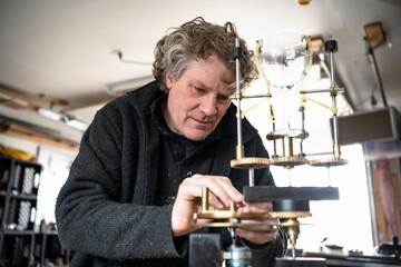 Focused male sculptor assembling wine glass sculpture in workshop