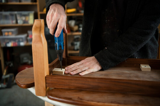 Male carpenter assembling furniture in workshop