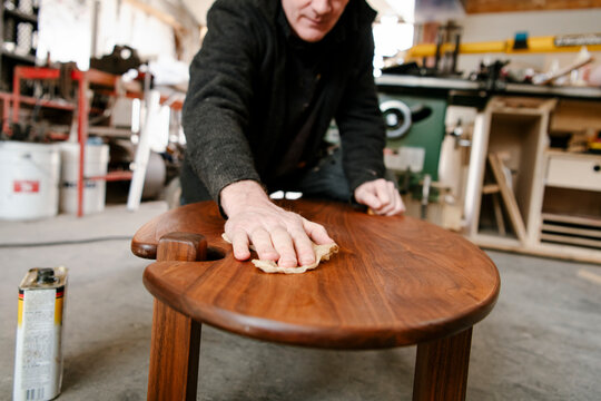 Male carpenter staining wood table in workshop garage