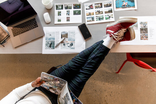 Overhead view of man reading with leg up on desk in creative workspace