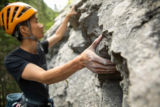 Young man in helmet rock climbing