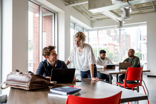 Mentor helping colleague at laptop in coworking space