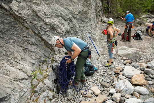 Rock climbers preparing equipment below rock