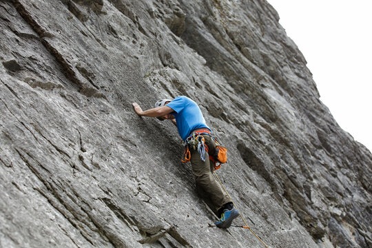 Senior male rock climber scaling steep rock face
