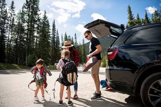 Family unloading camping equipment from car in sunny parking lot