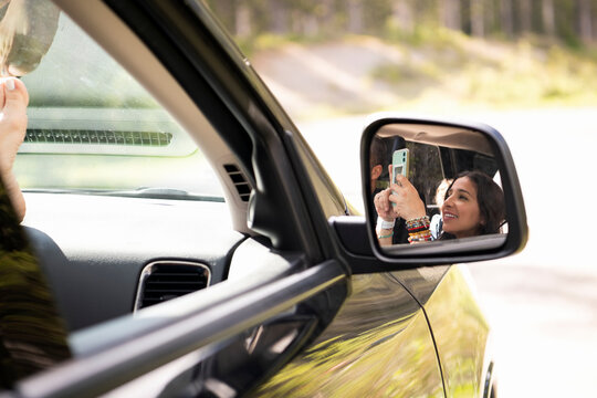 Woman using smart phone in car side view mirror