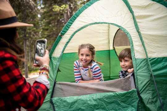 Mother with smart phone photographing kids in tent at campsite