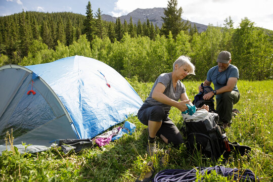 Mature couple with backpacks outside tent in sunny forest field