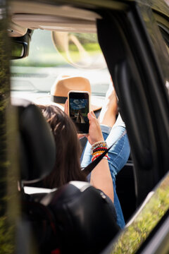 Woman using smart phone on road trip in car