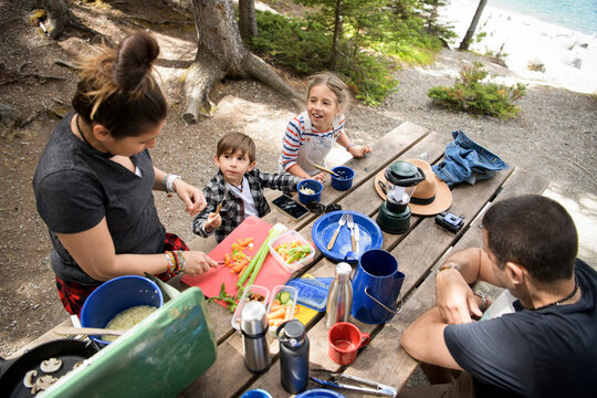 Family eating at campsite picnic table