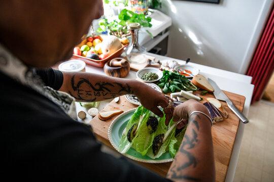 Man preparing lettuce wrap dish