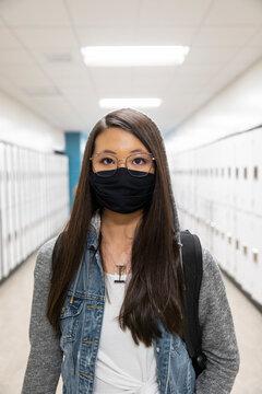 Student in school corridor wearing face mask