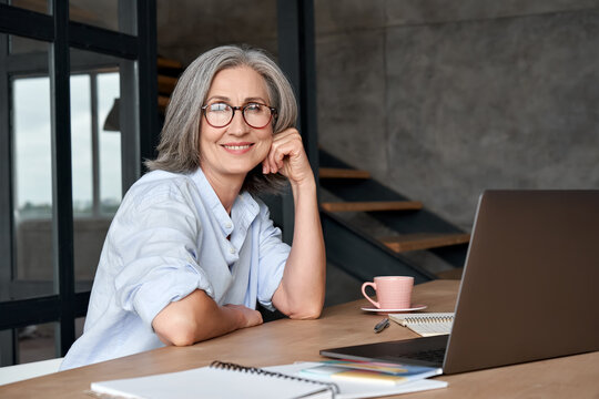 Smiling stylish mature middle aged woman sits at desk with laptop, portrait. Happy older senior businesswoman, 60s grey-haired lady wearing glasses looking at camera sitting at office table. Headshot.
