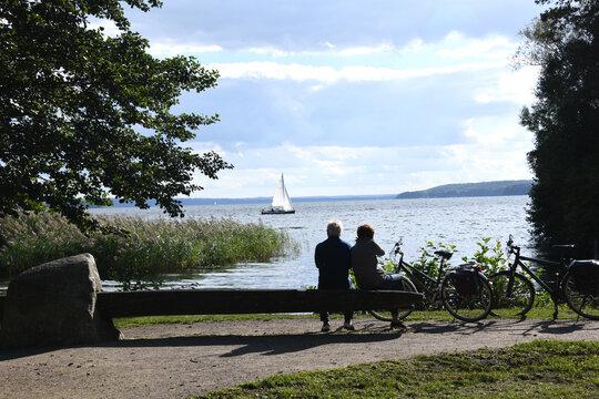 Entspannung am Tollensesee in Neubrandenburg. Ein Paar bei der Rast beobachtet ein Segelschiff am Ufer. Sie entspannen sich auf einer Bank nach einer Fahrradtour.