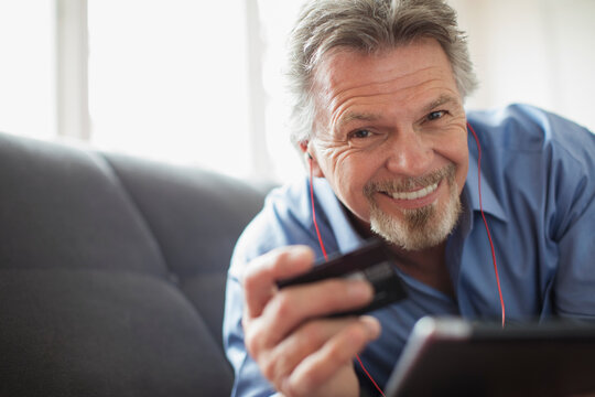 Portrait smiling senior man with headphones and credit card