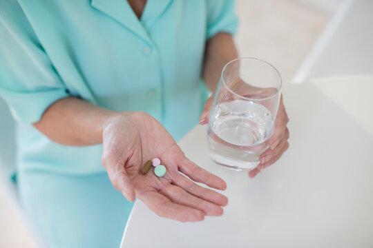 Senior woman taking vitamins with water