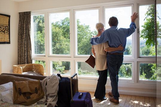 Affectionate senior couple hugging at sunny house rental window