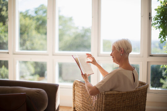Senior woman relaxing and reading book in sunny living room