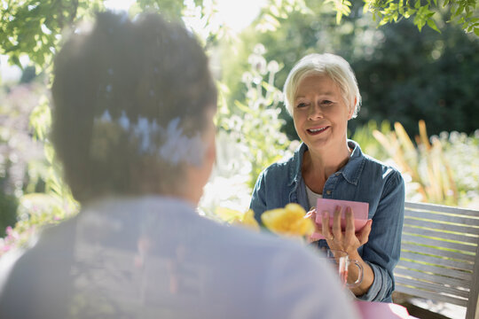 Happy senior woman opening gift from husband on sunny summer patio