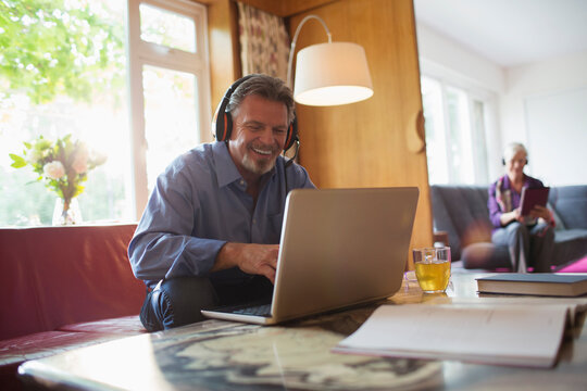 Happy senior man with headphones using laptop in living room