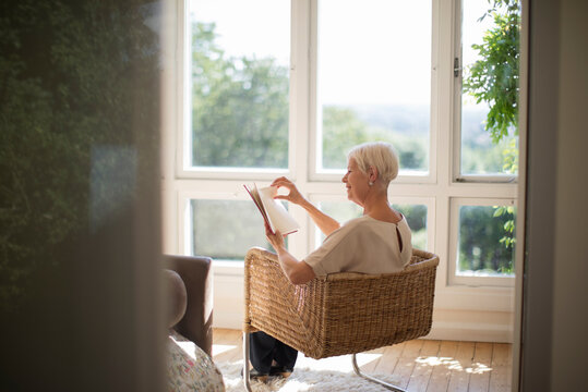 Senior woman relaxing and reading book in living room armchair