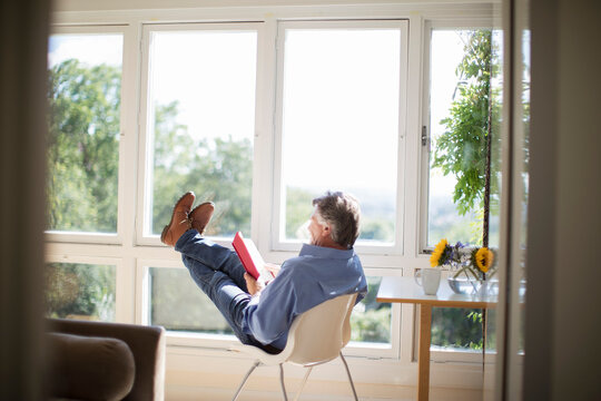 Carefree senior man reading book with feet up at sunny window