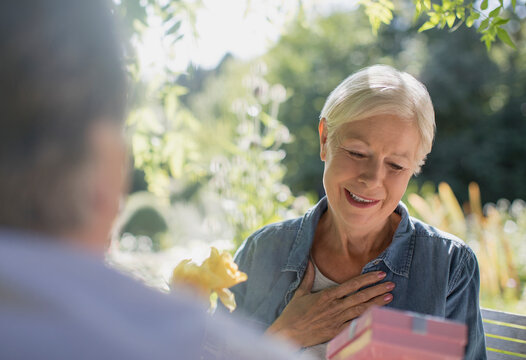 Happy senior woman receiving gift from husband on sunny patio