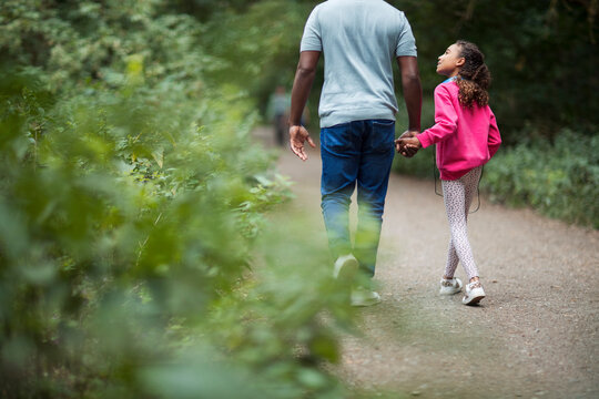 Father and daughter holding hands hiking on path in woods