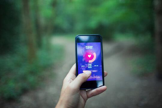 Close up POV runner using health app on smart phone screen