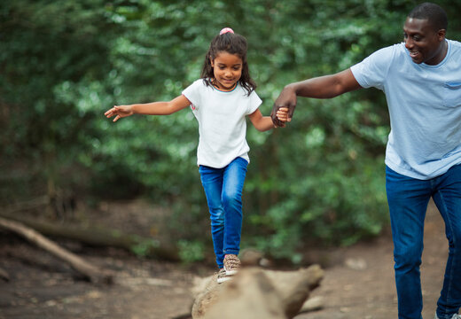 Father helping daughter balance on fallen log in woods