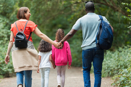 Affectionate family holding hands hiking on trail in woods