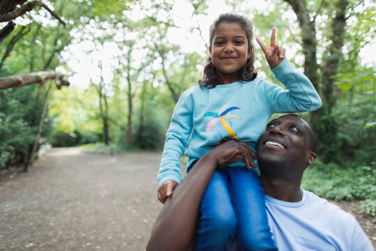 Portrait father carrying daughter gesturing peace sign in woods