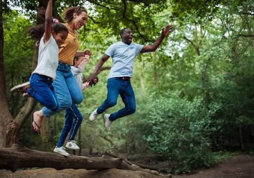Carefree family jumping off fallen log in woods