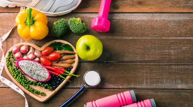 Top view of fresh organic fruit and vegetable in heart plate, shoes, sports equipment and doctor stethoscope, studio shot on wooden gym table, Healthy diet vegetarian food concept, World food day