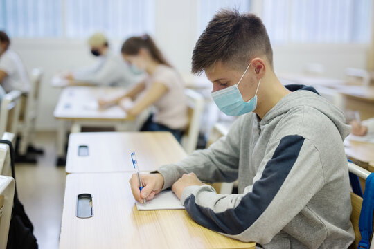 Portrait of teenager in protective face mask writing in workbook on lesson. New life reality during COVID pandemic