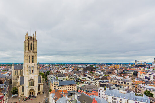 Aerial view of the Ghent cityscape, the facade of St Bavo Cathedral with its imposing tower surrounded by houses and buildings in the city center, cloudy day with a cloud covered sky in Belgium