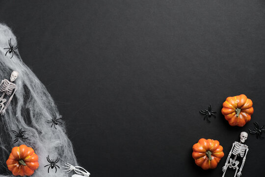 Mystery Halloween background with pumpkins, spiderwebs, skeletons, spiders on black table. Flat lay, top view, copy space.