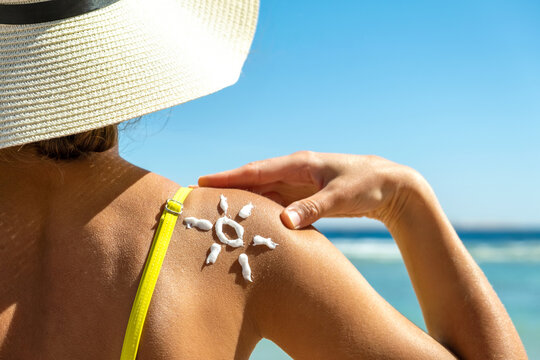 Back view of young woman tanning at the beach with sunscreen cream in sun shape on her shoulder. UV sunburn protection and sunblock skincare concept