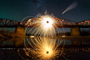 Spinning steel wool in abstract circle, firework showers of bright yellow sparks on long bridge reflected in river water under dark night starry sky.