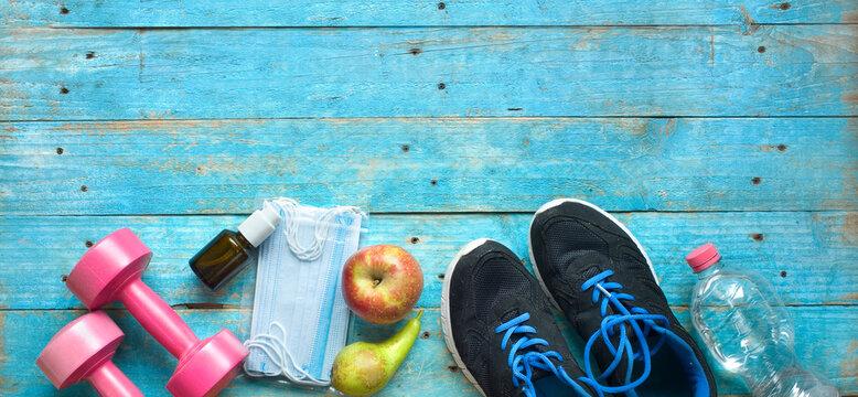 sport in times of coronavirus; corona mask, disinfectant spray,pair of runners, dumbbells, water,apple, pear,cornavirus policies concept