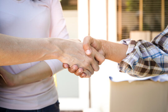 A home repair contractor shakes hands with her husband and wife for delivery after all finishes have been checked. The concept of housing improvement