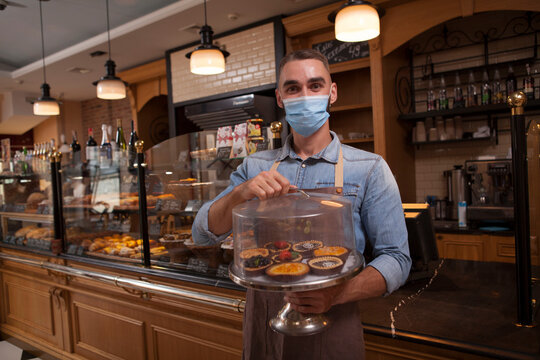 Cheerful male baker wearing medical face mask, working at his coffee shop selling delicious desserts during coronavirus pandemic