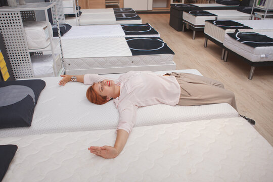 Happy female customer stretching, enjoying lying on orthopedic bed at home goods store